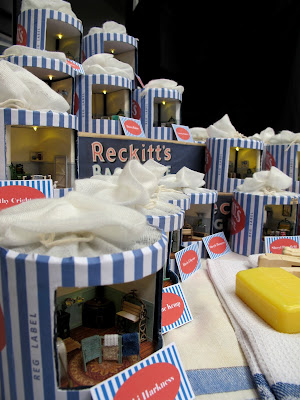 Display of Reckitt's bags containing miniature vintage laundries.