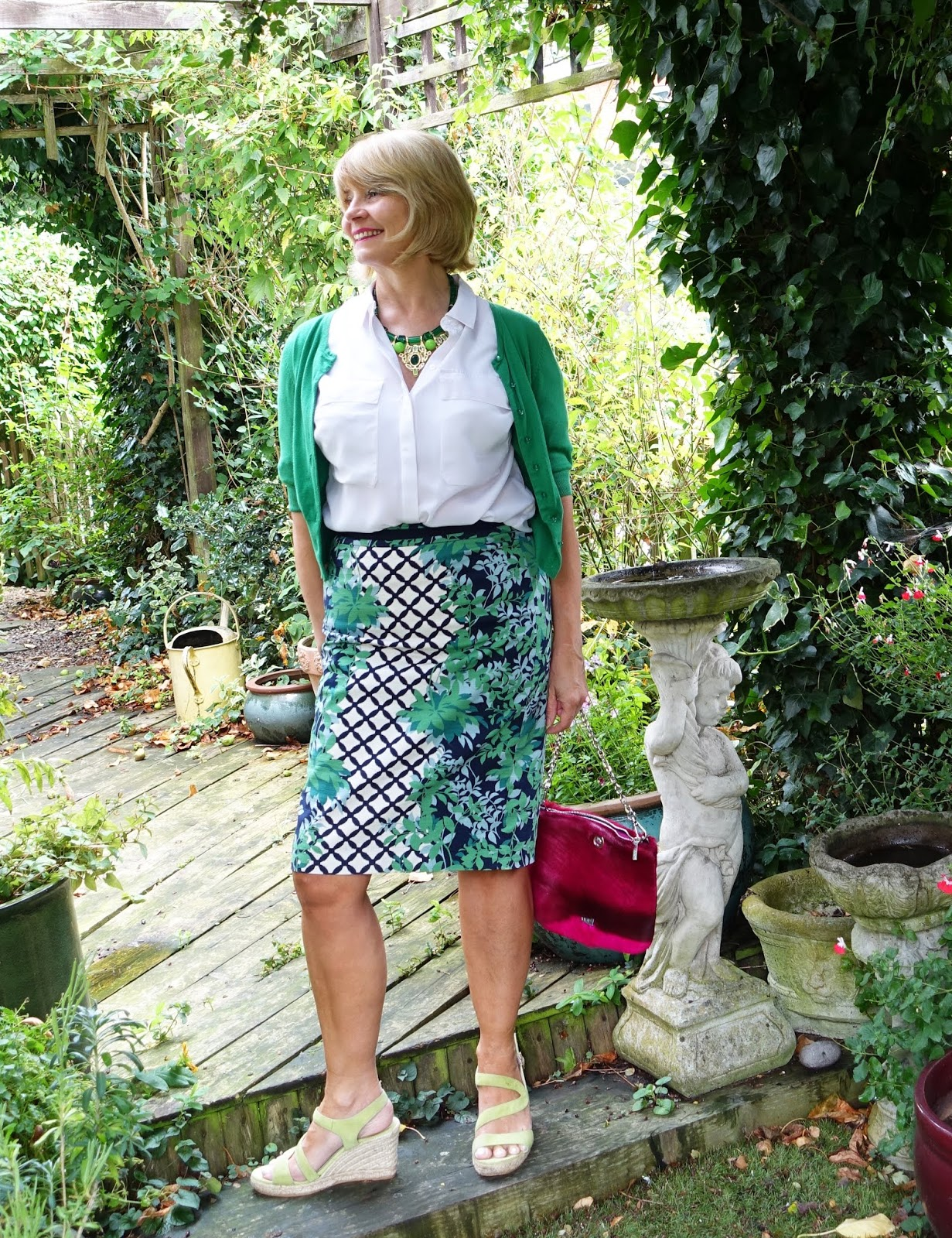 Garden shot of over 50s woman in green and white outfit with striking green necklace and pink bag