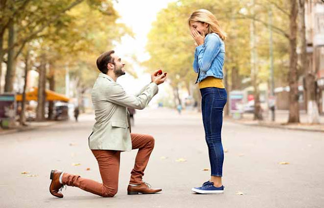 A guy on his knees proposing to a woman with a ring in his hands