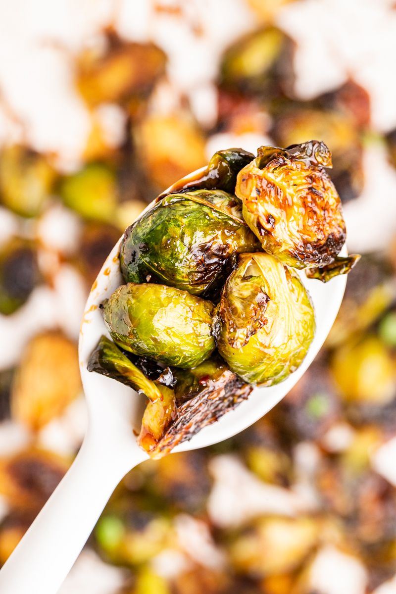 Closeup photo of a serving spoon full of Kung Pao Brussels Sprouts.