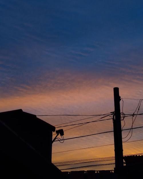 Vista do entardecer. Céu em tons de azul claro, azul escuro, rosa e laranja.