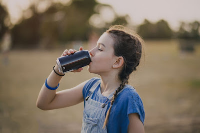 A girl is drinking cola