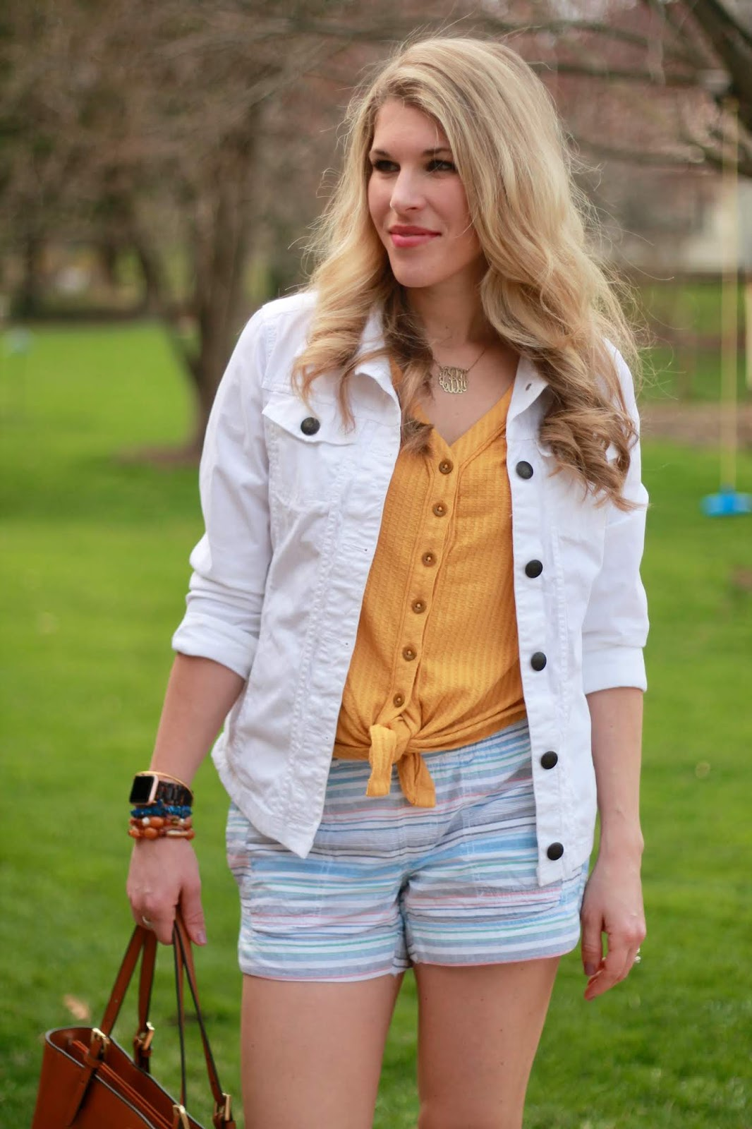 yellow button up, white denim jacket, striped blue shorts, aventura spring outfit, orange lace up sandals, cognac leather tote,