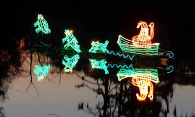 A green and white neon decoration, reflected in water, of Santa in a boat being pulled by gators.