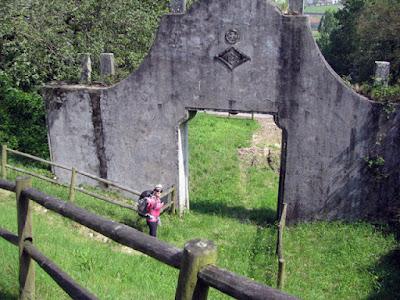 peregrina de Santiago de compostela apontando para um arco na paisagem