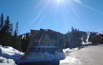 Monarch Mountain sign with snow and sunshine all around.