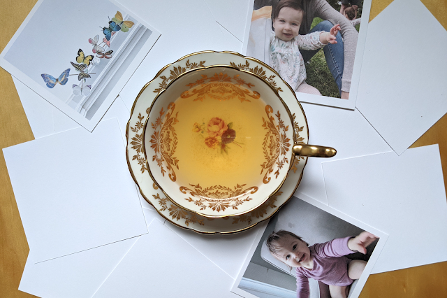 A styled flatlay of a vintage teacup over photo prints