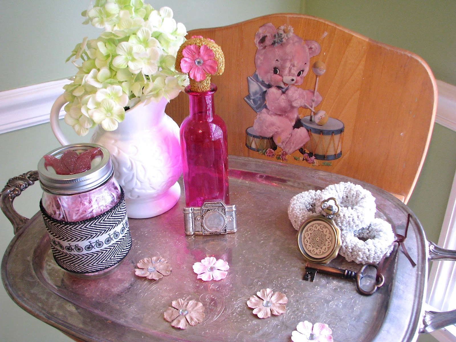 Vintage camera, skeleton key, vintage colored bottle and flowers on a silver tray