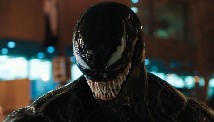 Imagem: o personagem Venom, um monstro preto com veias brancas pelo o seu corpo com um par de olhos brancos e leitosos e um sorriso de dentes muito grandes e afiados.