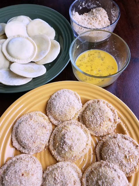 ravioli next to small bowls of bread crumbs, egg wash and bread crumb coated ravioli