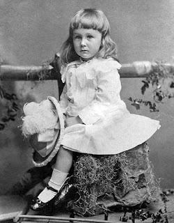 Menino de cabelos longos, vestido e chapéu na Era Vitoriana