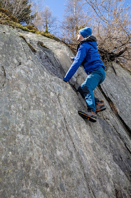 A young white man in a blue rain jacket and the SCARPA Zodiac Plus GTX boots climbs a rock slab.
