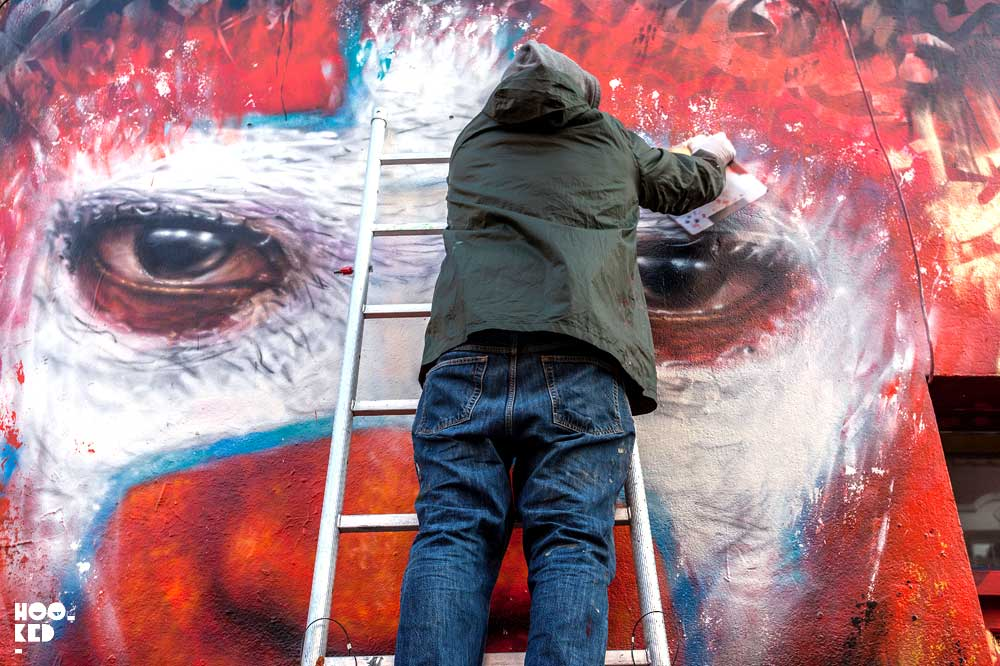 Dale Grimshaw adding the finishing touches to his Hanbury Street Mural in London.
