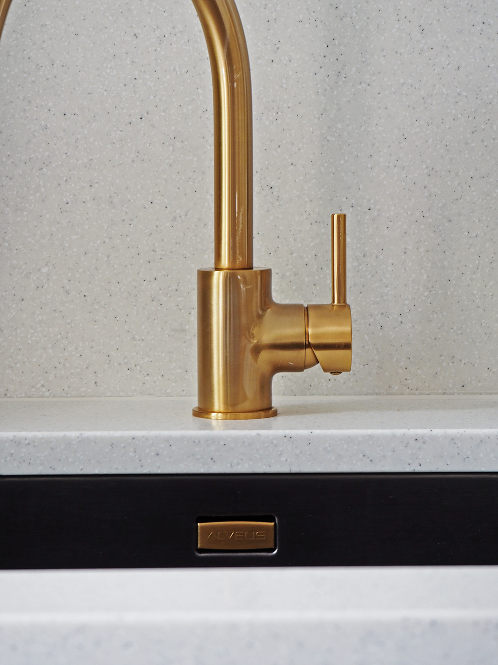 French For Pineapple Blog - close up of gold brass contemporary kitchen tap and pale flecked mistral mist worktop and undermounted anthracite sink