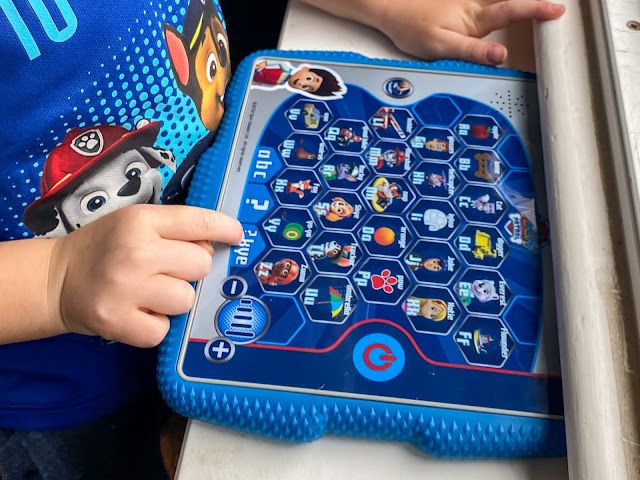 Close up of child playing on the PAW Patrol toy tablet to review it