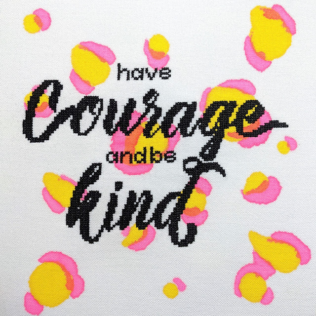 cross stitch lettering in modern calligraphy font with the words 'have courage and be kind' stitched on white fabric with pink and yellow leopard print