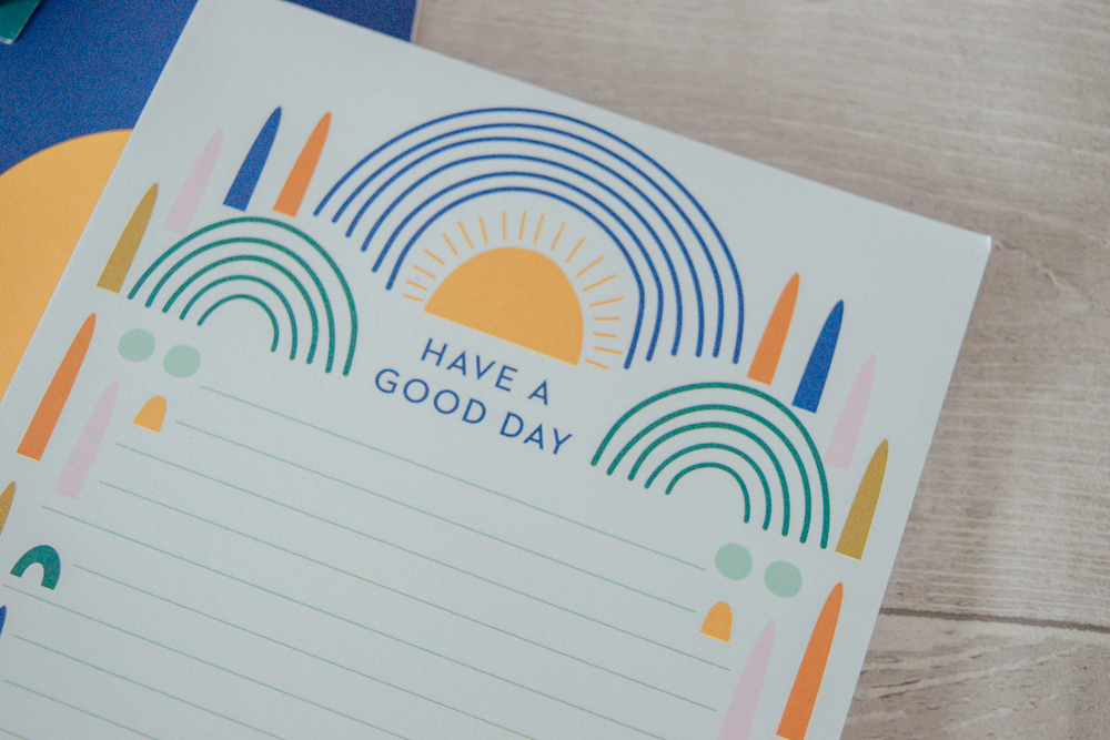 A notepad with the quote 'have a good day' on the top