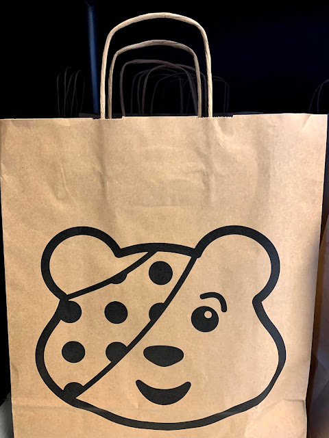 brown paper bag with Pudsey Bear face on