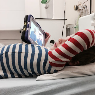 boy in his PJs on a hospital bed