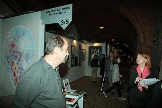 Przedstawiciel galerii z Paryża rozmawia ze zwiedzającymi