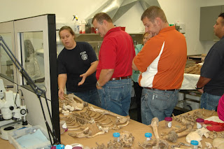 Teachers gather around human bones at the Southest Texas Applied Forensic Science Facility