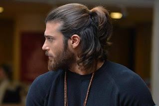 A mascular guy in stylish ponytail hairstyle.