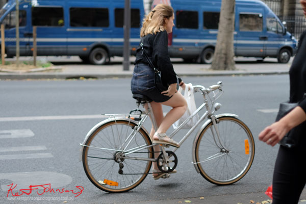 Woman in black blouse and denim skirt riding a silver Mixte bike. Paris photos by Kent Johnson for Street Fashion Sydney.