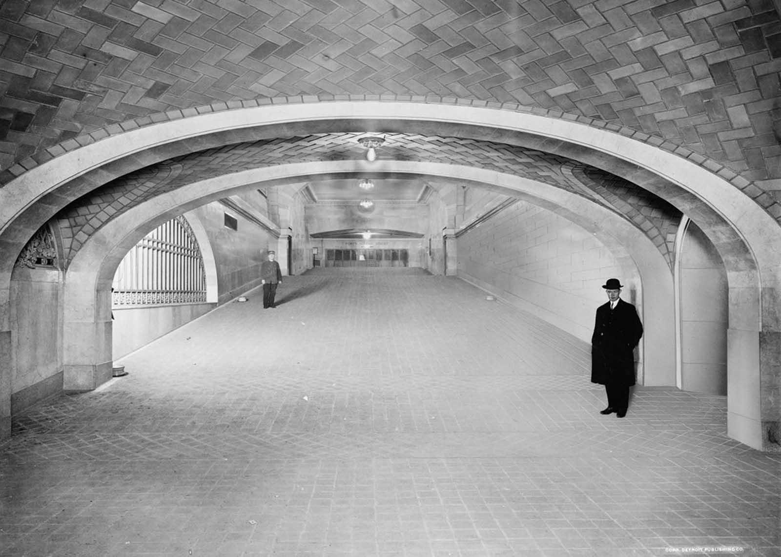 Los hombres se paran en una pendiente hacia el vestíbulo suburbano, Grand Central Terminal, ca 1912.