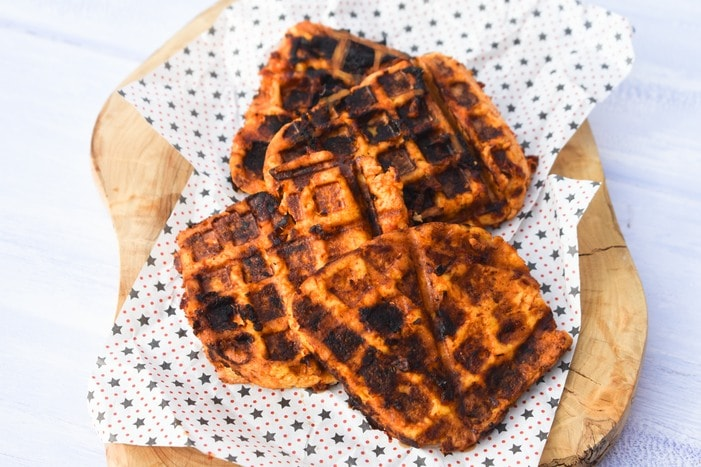 Tofu grilled in a waffle maker on a wooden board