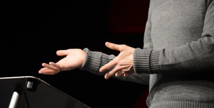 A imagem mostra mãos jovens de um pregador iniciantes trajando mangas longas na cor cinza em frente ao púlpito pela primeira vez.