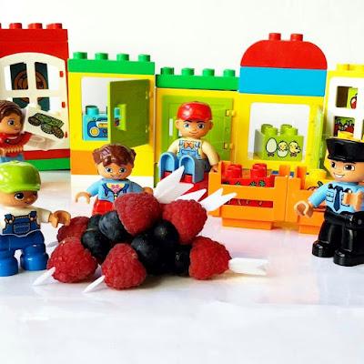 Figuras y piezas de Lego duplo acompañan unas brochetas de frambuesas y arandanos