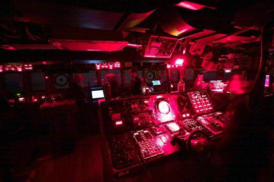Il ponte illuminato di rosso di un cacciatorpediniere della classe Arleigh Burke di notte.