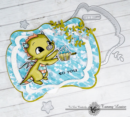 See You In The Center and Happy the Dragon products from TLC Designs paper craft products store.  Combined with the Dragons in Winter digi papers and the Star Spangled Confetti Die, the card is a Wintery delight!