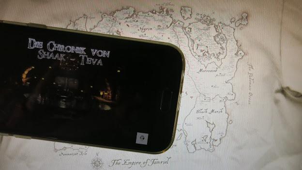 Vor der Landkarte des Kontinents Tamriel (wie er auf einem Shirt des Herstellers Bethesda dargestellt ist) aus dem Spiel 'The Elder Scrolls: Skyrim' liegt ein Smartphone, auf dem ein Fanfiction-Hörspiel dazu läuft