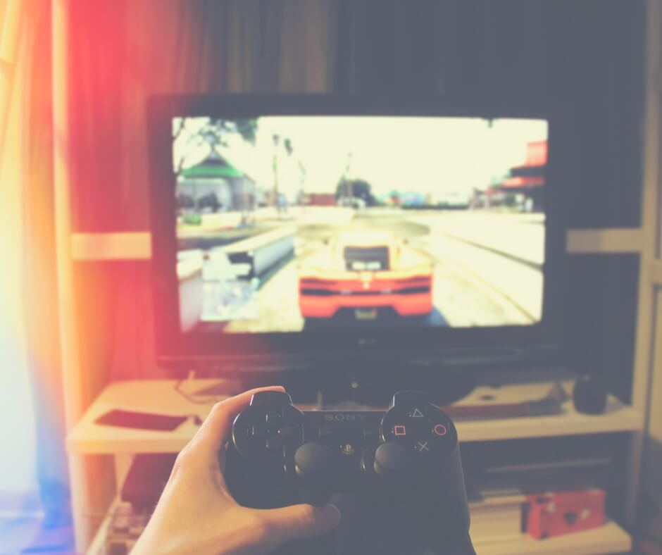 "A boy's hand holds a playstation controller, in the background is a large TV with a car on the screen. Image for ""Teaching your children about online gaming""."