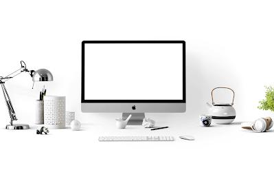 جهاز أبل ماكنتوش على مكتب أبيض بجانبه أدوات مكتبية