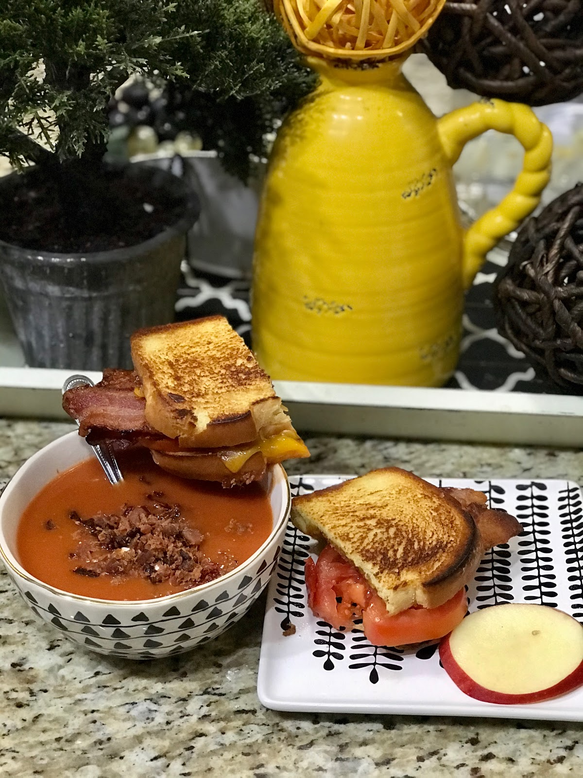 Cheese sandwich paired with a side of tomato soup and topped with bacon, sour cream,dried tomatos