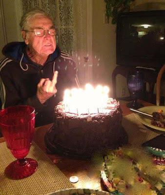 Lustiger alter Mann feiert Geburtstag mit Kuchen und Stinkefinger