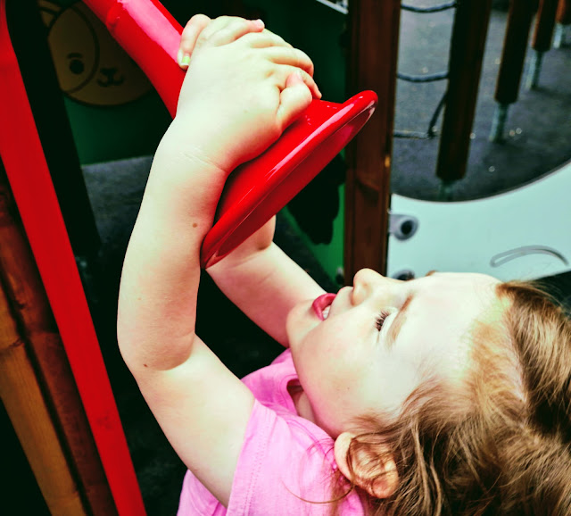 Image of a young girl/toddler playing on a playground and singing into a red speaker.