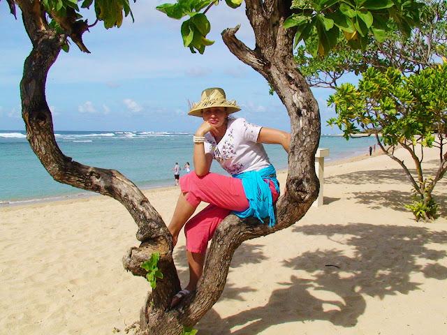 Изображение девушки на дереве на побережье океана, остров Бали, Индонезия