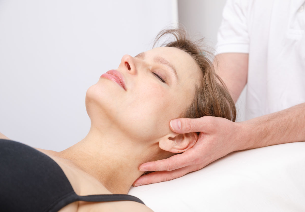 A male craniosacral therapist inducing a still point on a female client.