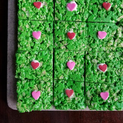 green rice krispie treats with red and pink hearts in the middle for Grinch treats