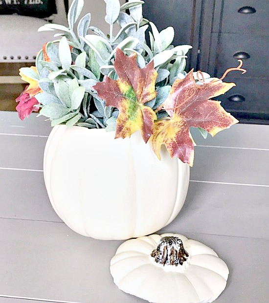 Add fall leaves to a faux pumpkin for centerpiece
