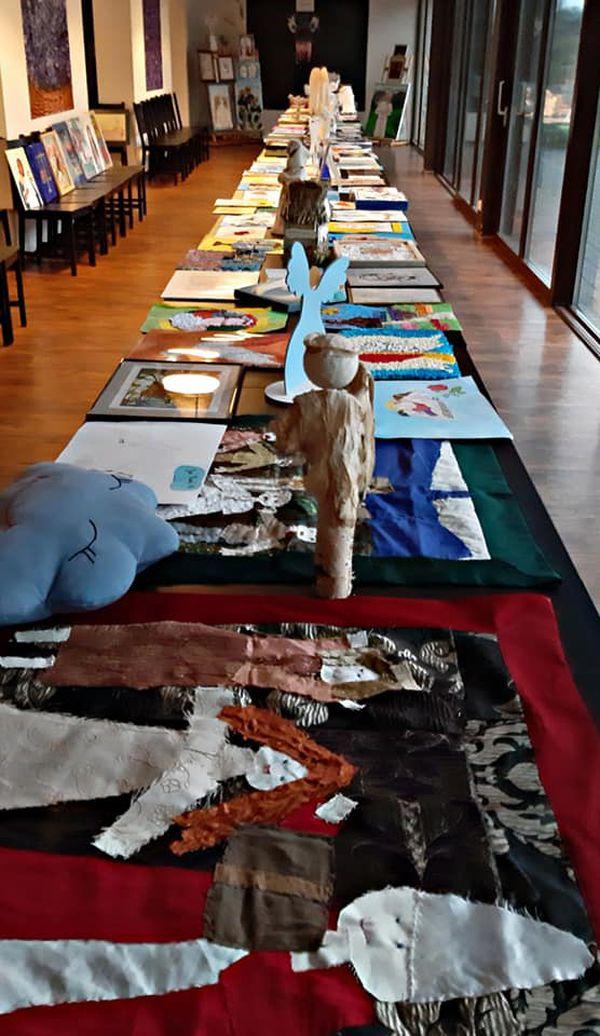 Na długim stole są prace artystyczne osób z niepełnosprawnościami