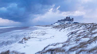 Bamburgh Castle and sand dunes after snowfall in Northumberland, England