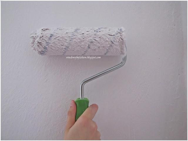 Ręka malująca ścianę wałkiem