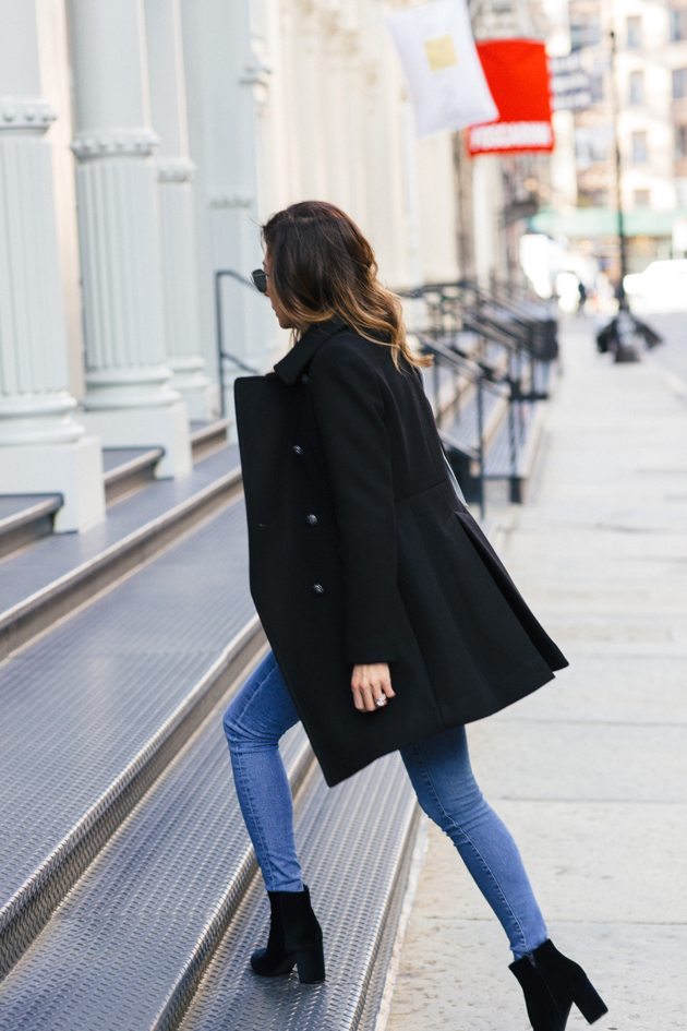 Walking up stairs in Soho showing back pleats of Trina Turk military style pea coat