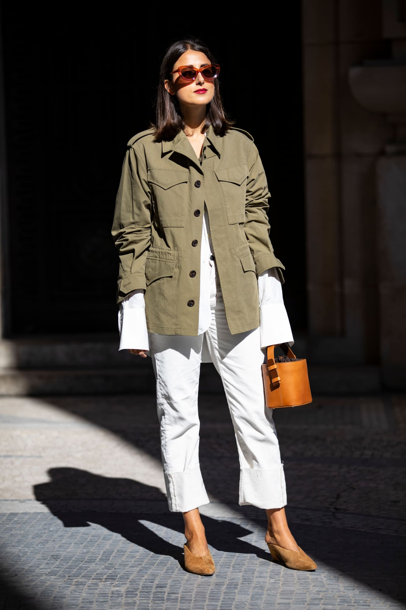 Spring outfit idea and wardrobe staples — green utility jacket, oval sunglasses, white jeans, mule heels