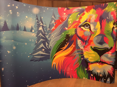 photo of mural showing a rainbow coloured lion against a background of a snowy forest