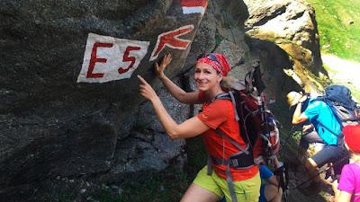 Eine Wanderin, die an einem Felsen steht und auf die Markierung des E5 zeigt